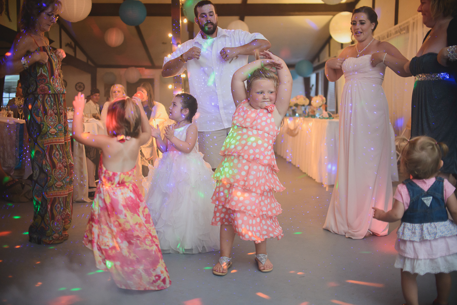 funny children and guests dancing to chicken dance at rustic wedding reception