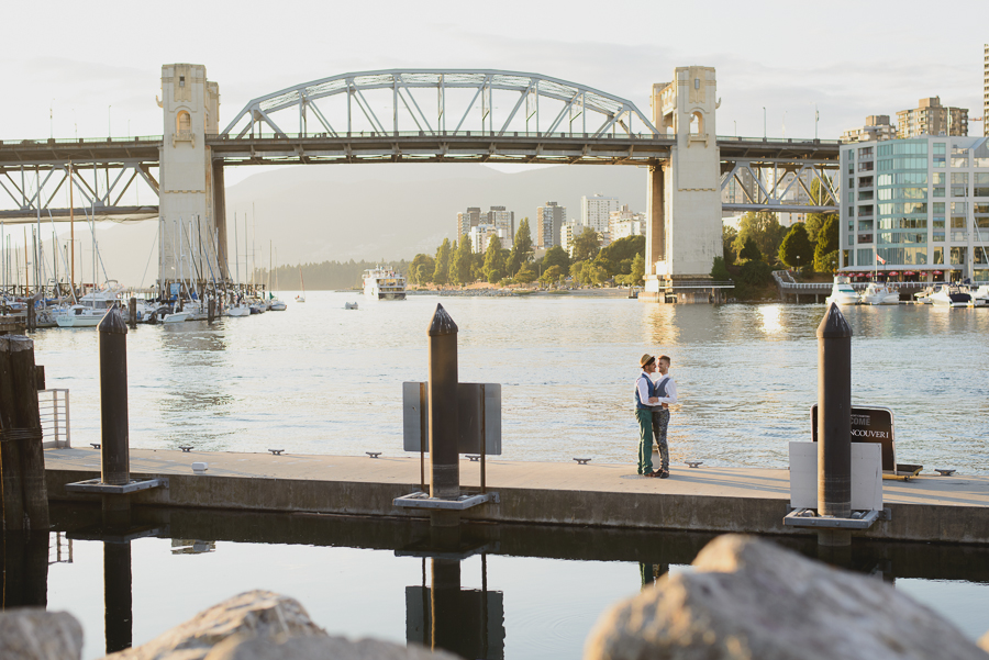 same-sex couple on dock with reflection in front of Burrard Street Bridge on Granville Island