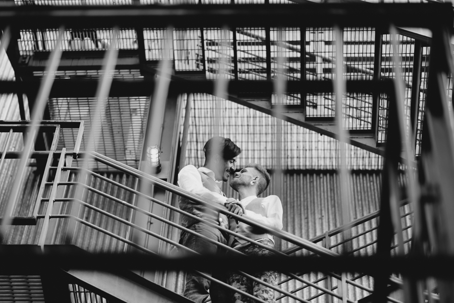gay couple on staircase industrial engagement photo | gay anniversary session