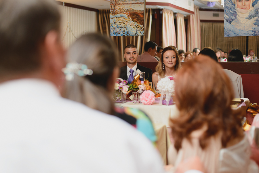 bride and groom listening to toasts at wedding reception