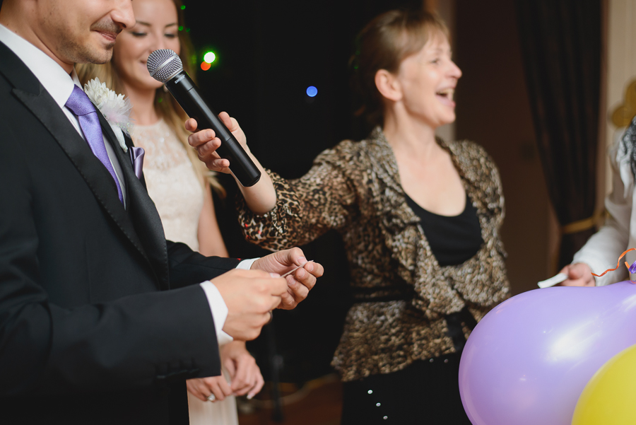 bride and groom popping balloons to determine household responsibilities after wedding