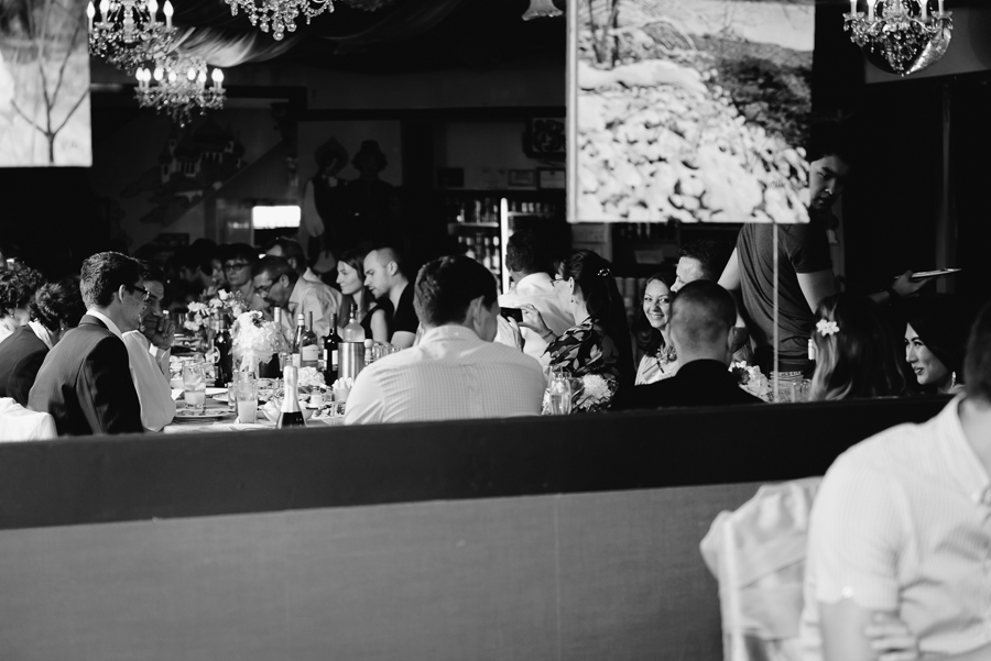 candid black and white photo of guests eating dinner at wedding reception at Russian House Restaurant in Coquitlam, BC