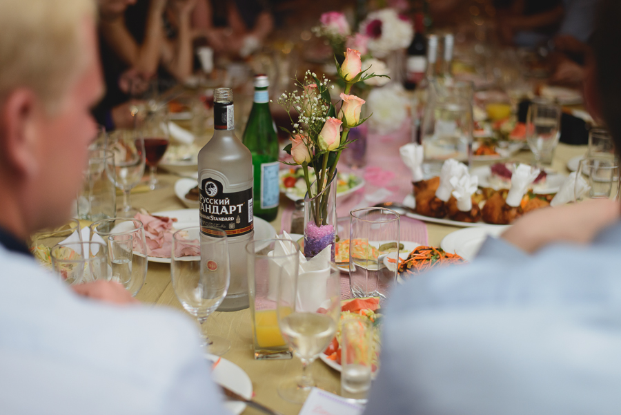 Vodka bottle and roses centerpieces at wedding reception