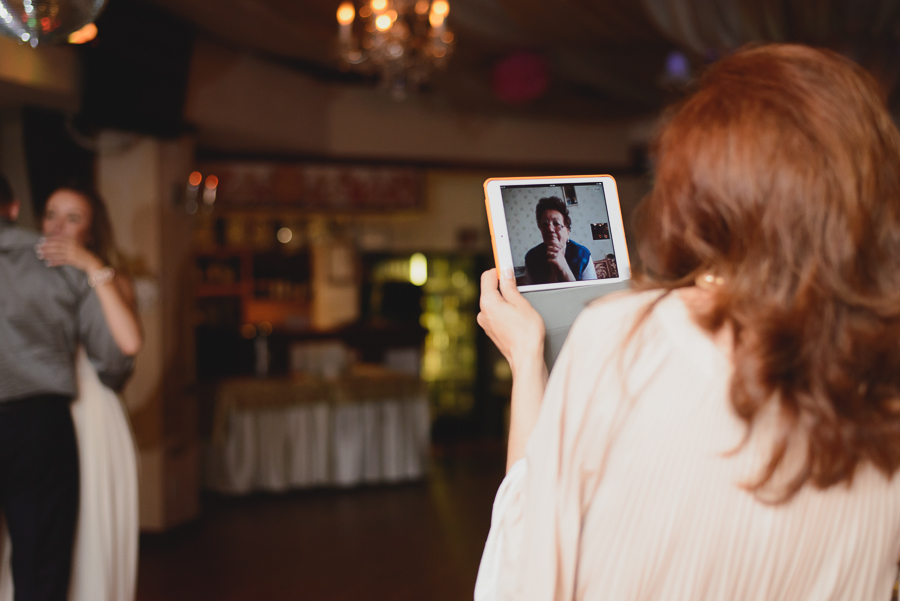 grandmother watching father daughter dance at wedding reception on Skype