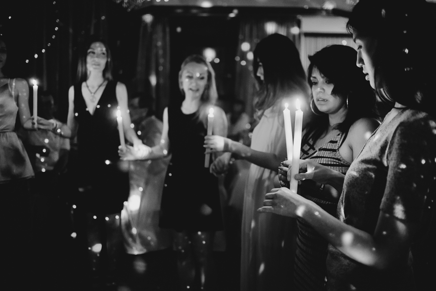 female guests in circle with candles at wedding reception