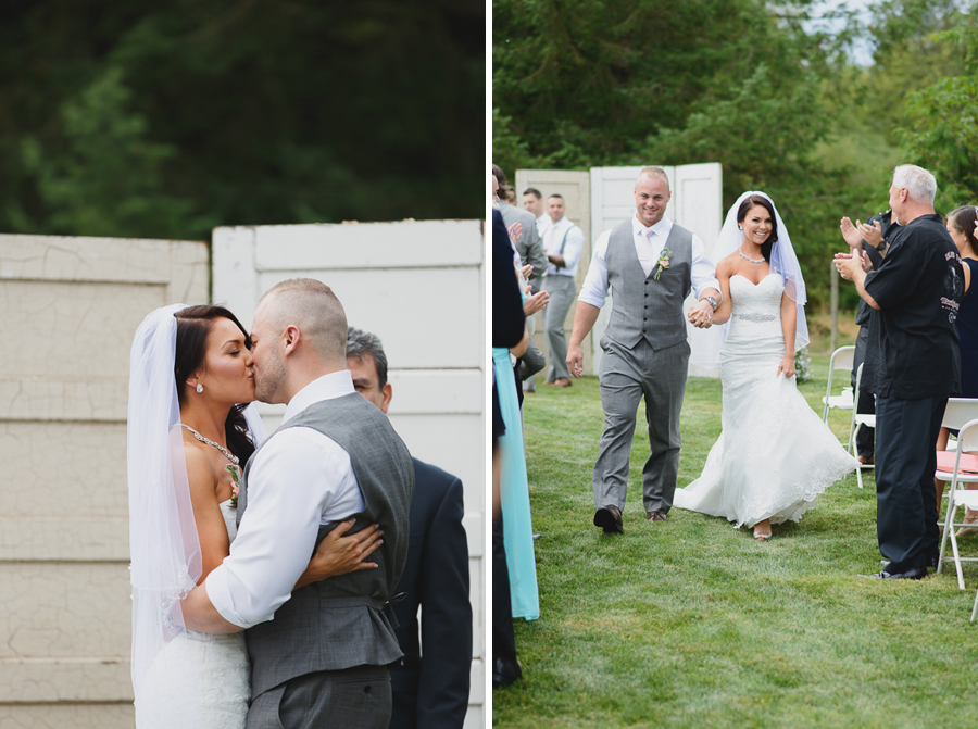 first kiss in front of rustic doors ceremony back drop at shabby chic family farm wedding