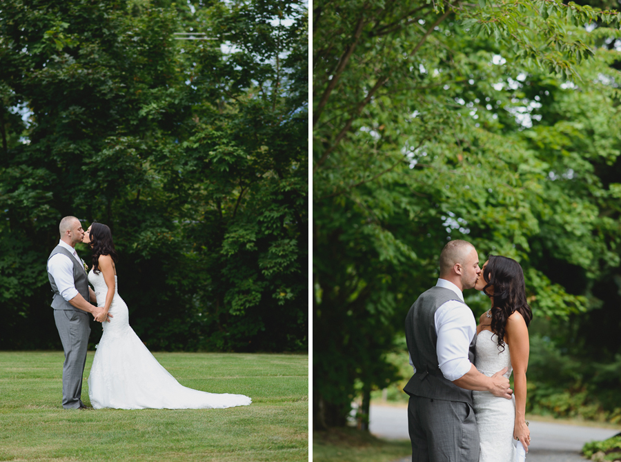 bride in lace fit and flare dress kissing groom in grey vest with light pink tie kissing