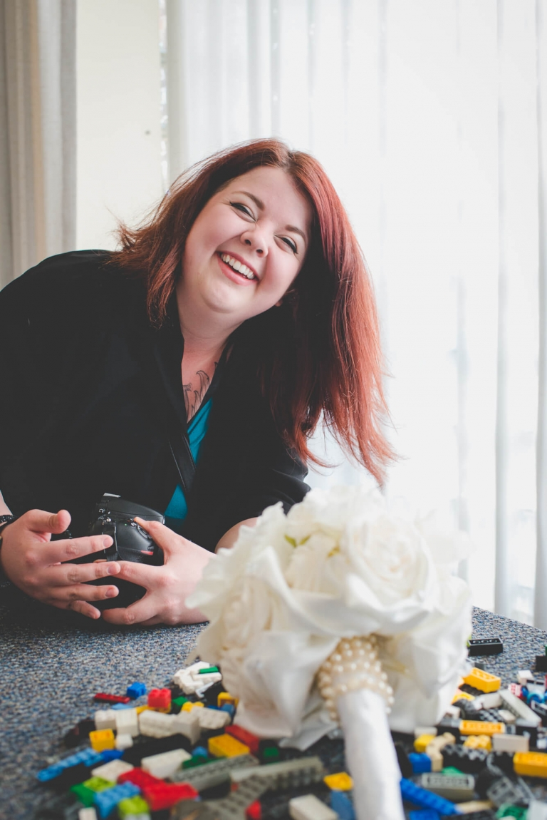 Vancouver wedding photographer behind the scenes laughing while setting up bouquet shot in a pile of LEGO