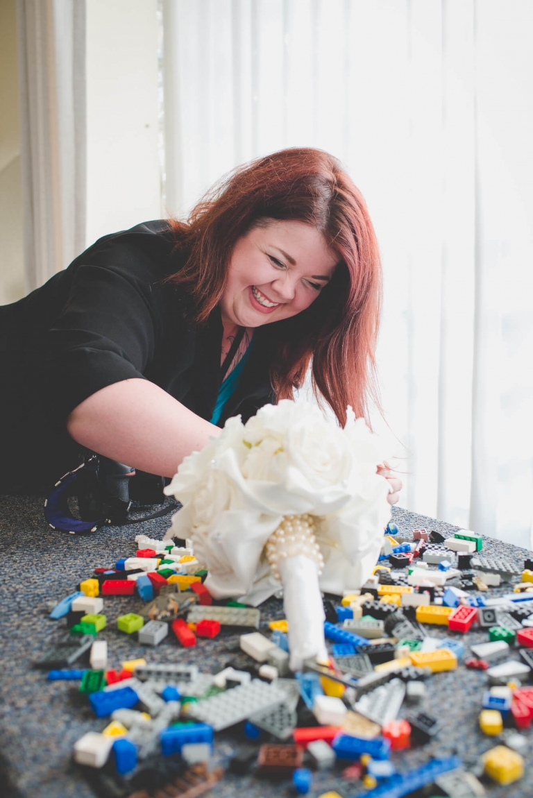 Vancouver wedding photographer behind the scenes setting up bouquet shot in a pile of LEGO