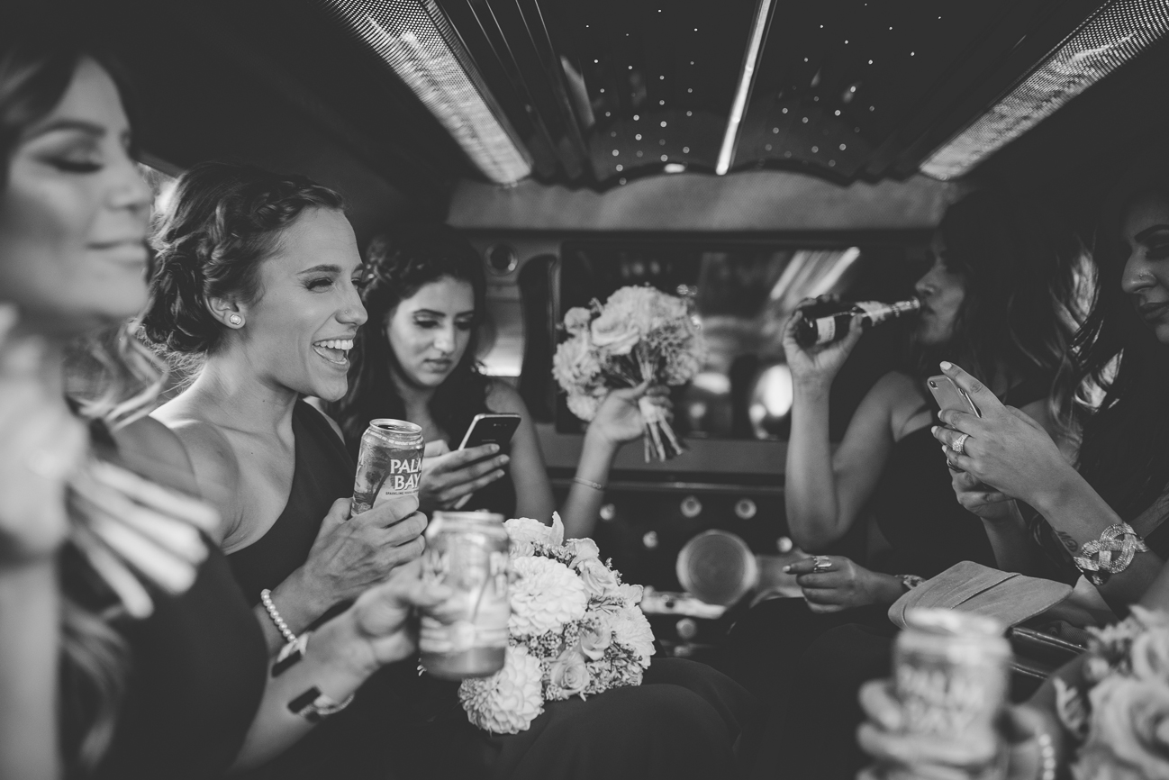 bridesmaids drinking and taking selfies in limo on wedding day