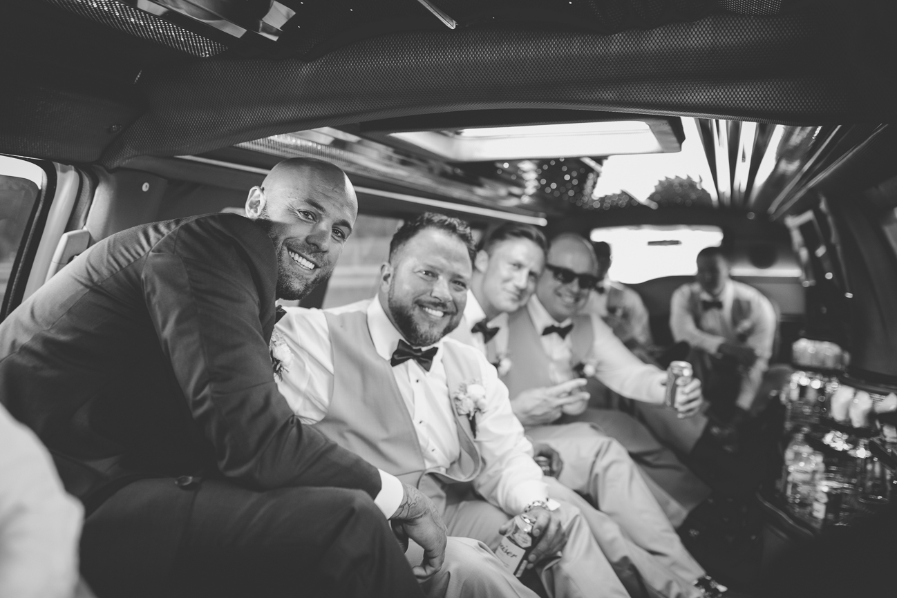 groom drinking with groomsmen in limo on wedding day