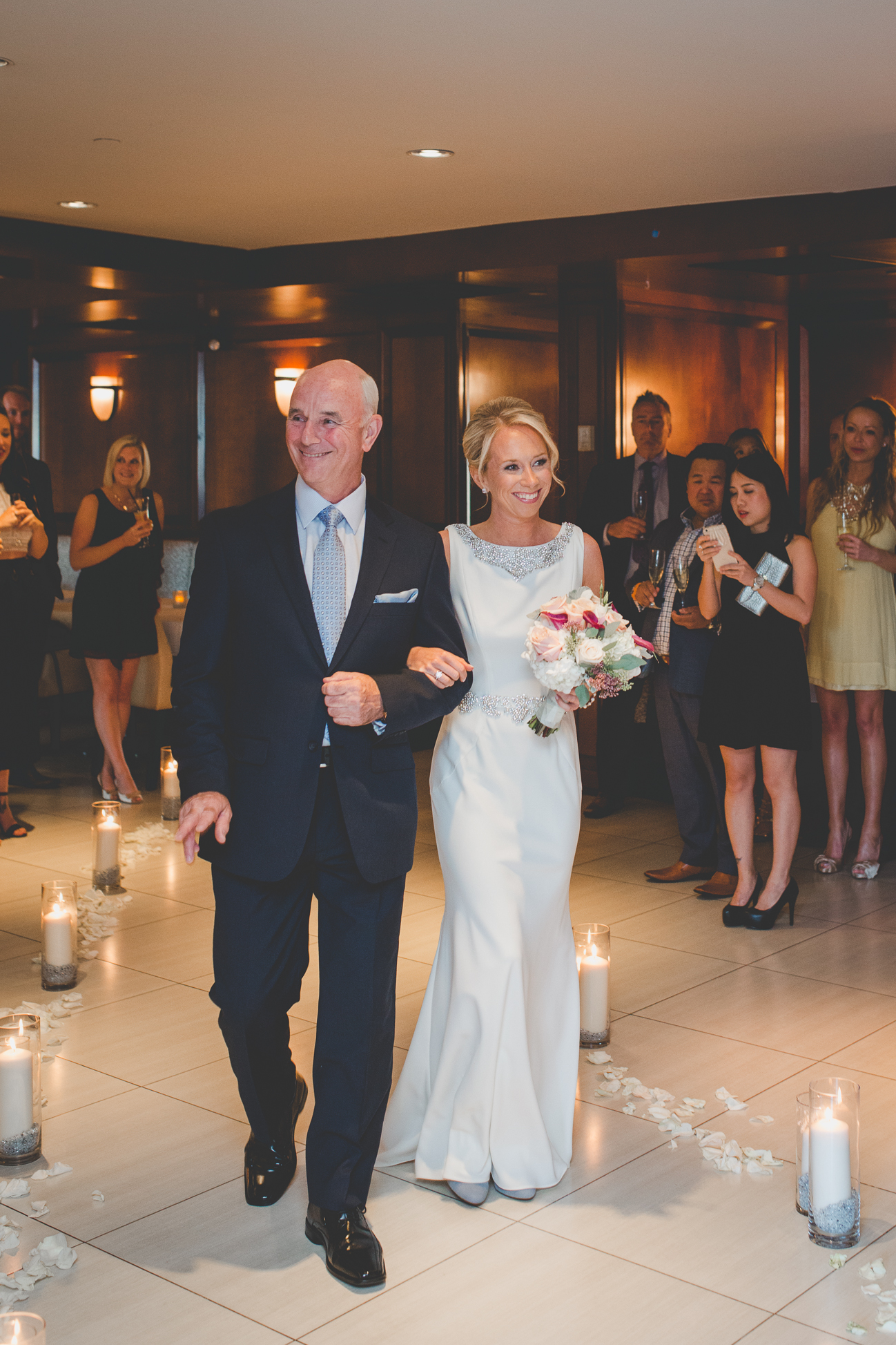 bride in elegant beaded wedding dress walks down aisle with proud father at Dockside Lounge