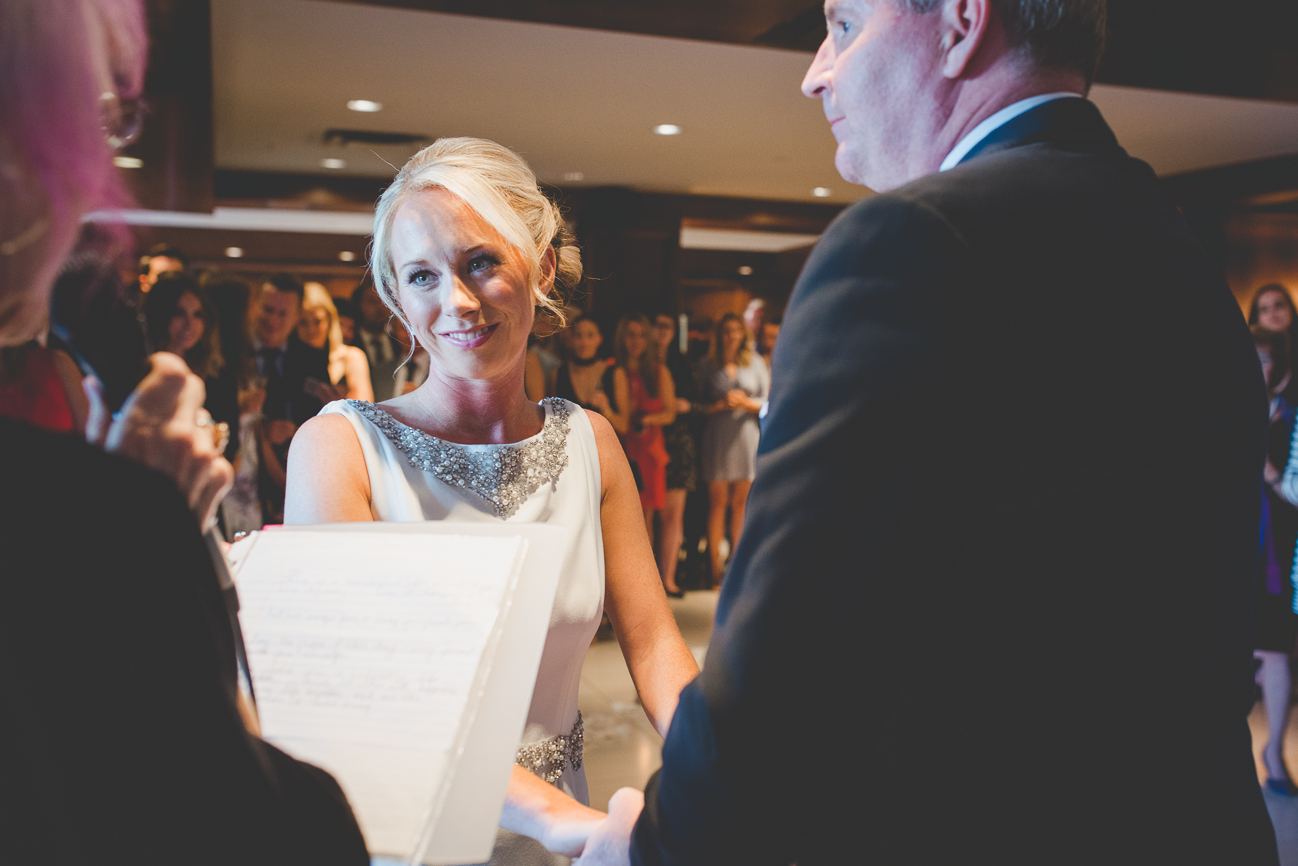 bride smiles at the officiant during vows while family and friends watch