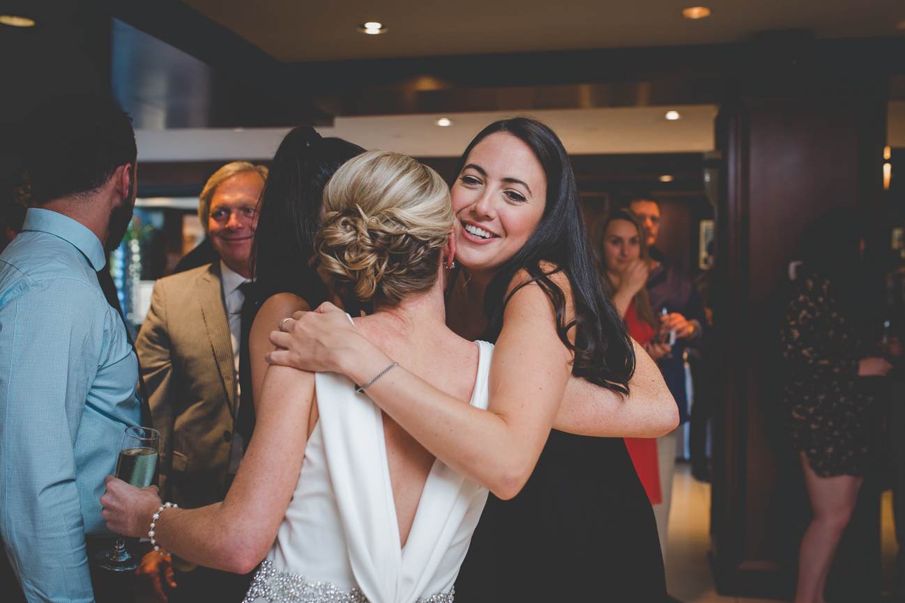 bride hugs friends during receiving line after wedding ceremony at Dockside Lounge on Granville Island