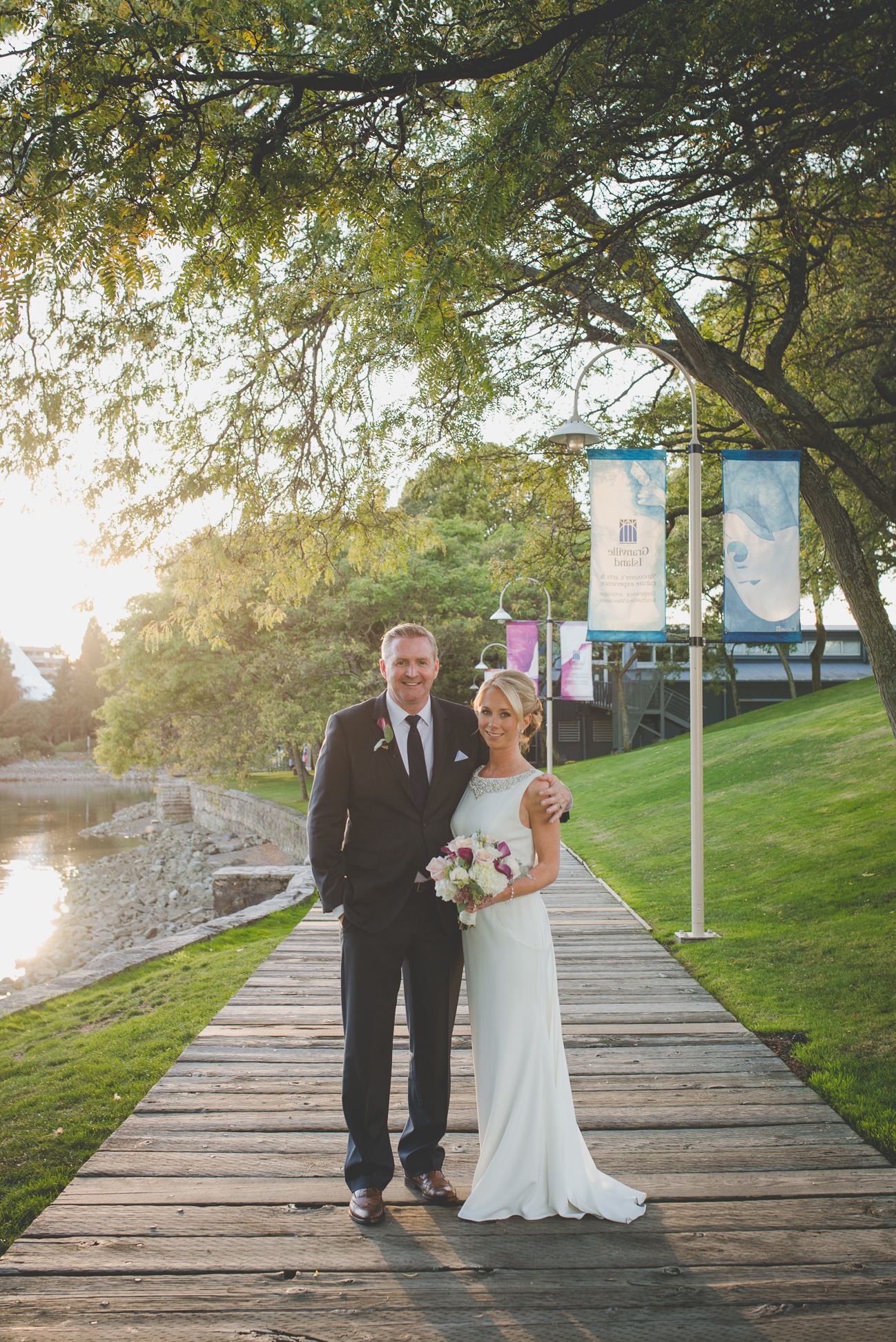 bride and groom stand on boardwalk on Granville Island after wedding ceremony at Dockside Lounge