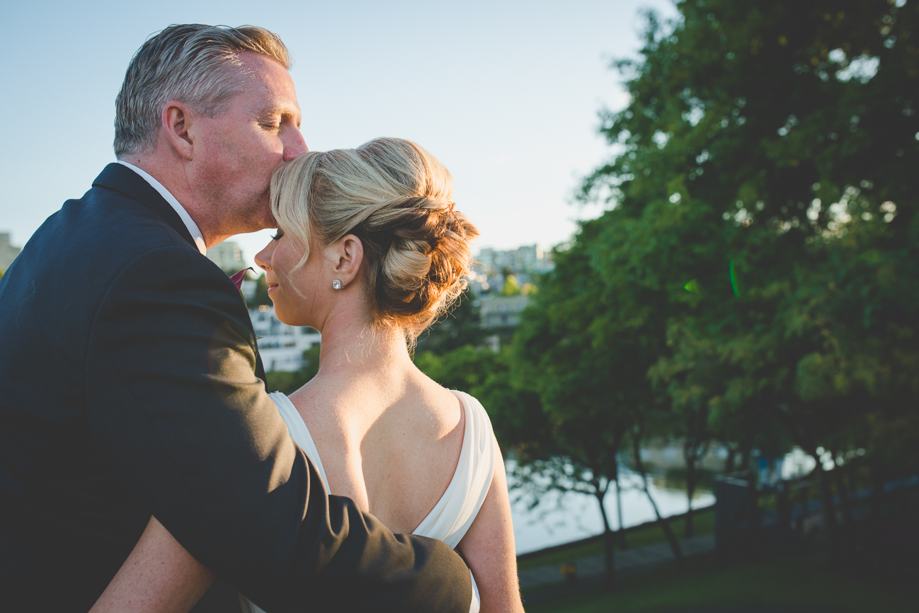 groom kisses bride on forehead during sunset at Granville Island