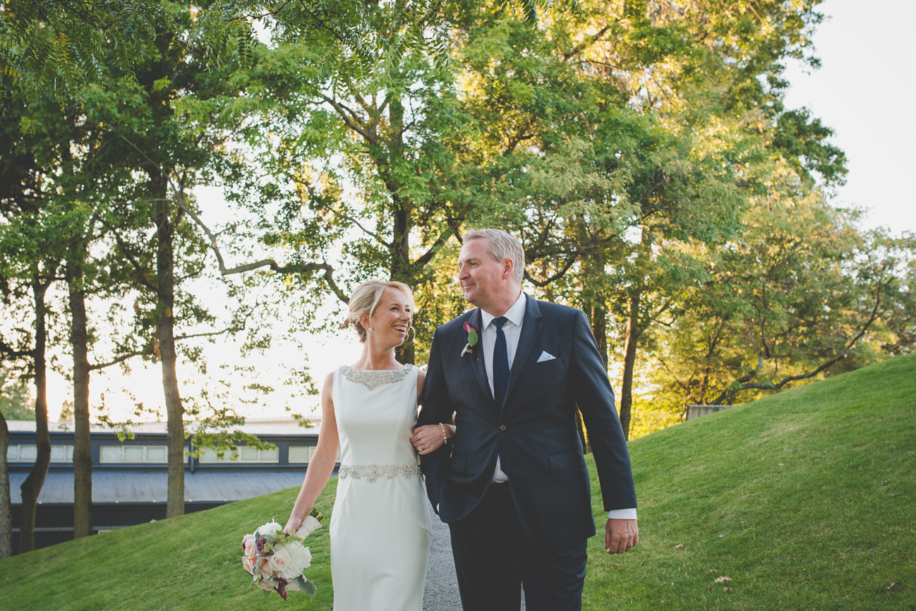 bride with romantic up-do and elegant wedding dress with beaded neckline and belt laughs and walks arm in arm with groom after wedding ceremony