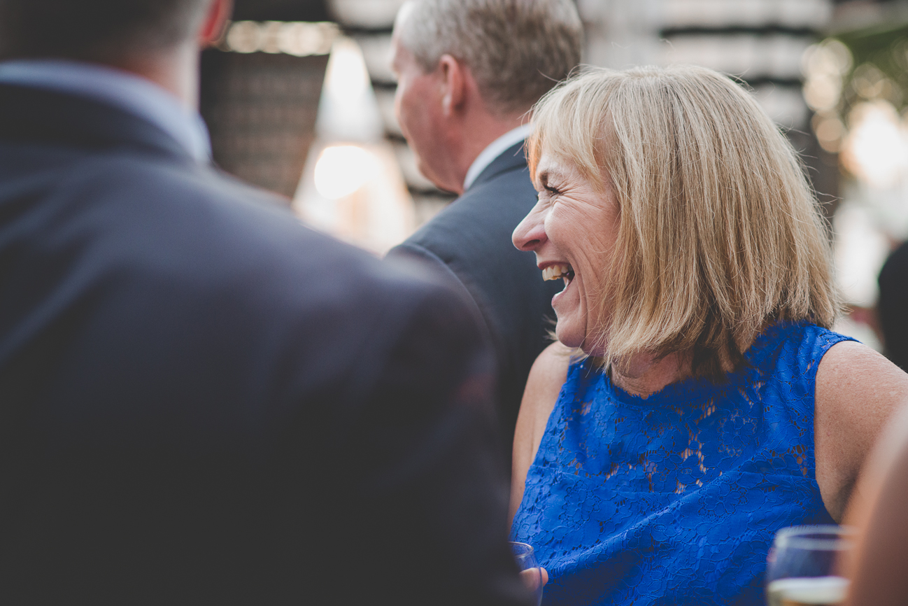 mother of the bride laughs with guests during cocktail hour at Granville Island wedding reception