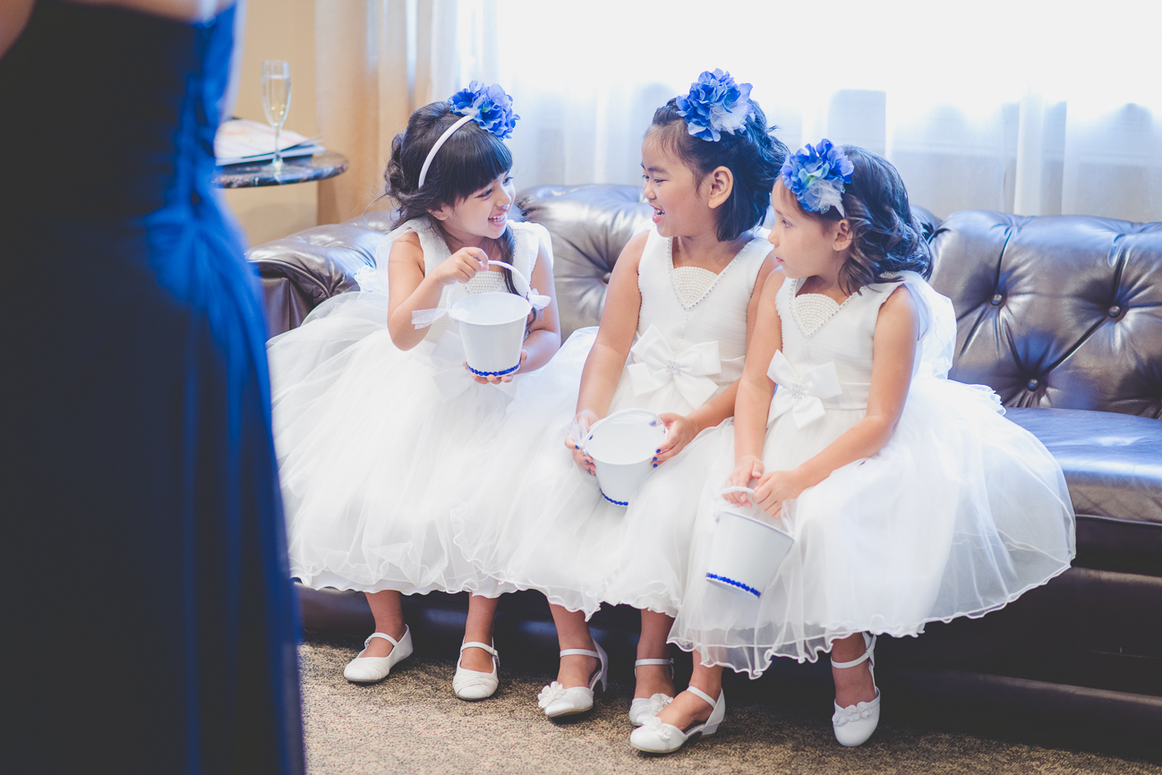 three flower girls in matching dresses and cobalt blue flower headbands with white pails laughing before wedding ceremony