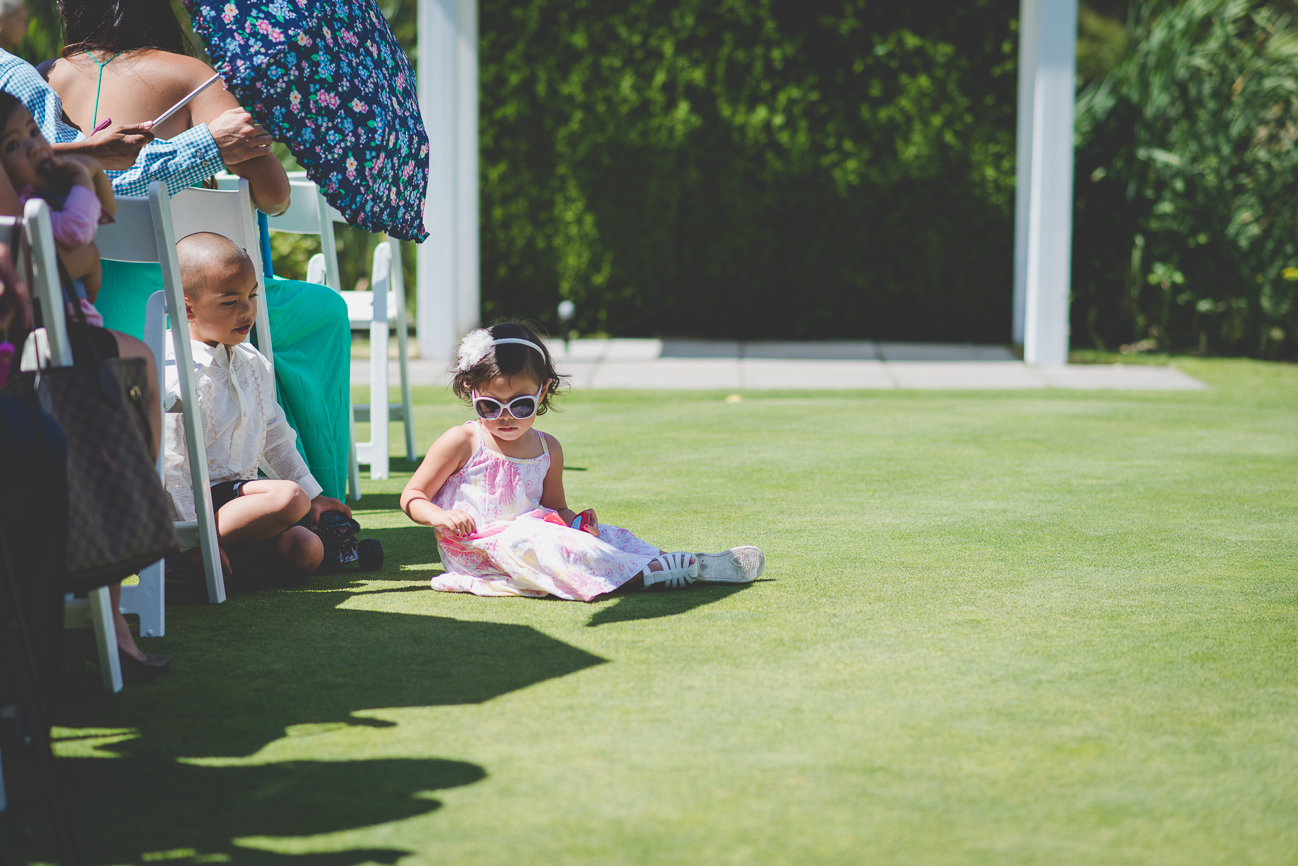 child guest in large sunglasses sitting on ground at golf course wedding before wedding ceremony