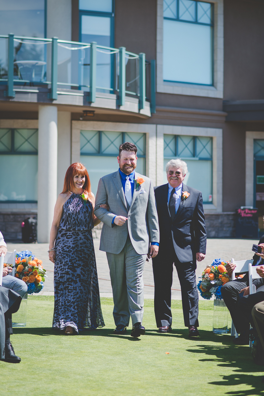groom in grey suit with cobalt blue shirt, white tie and white pocket square walking down the aisle with his parents
