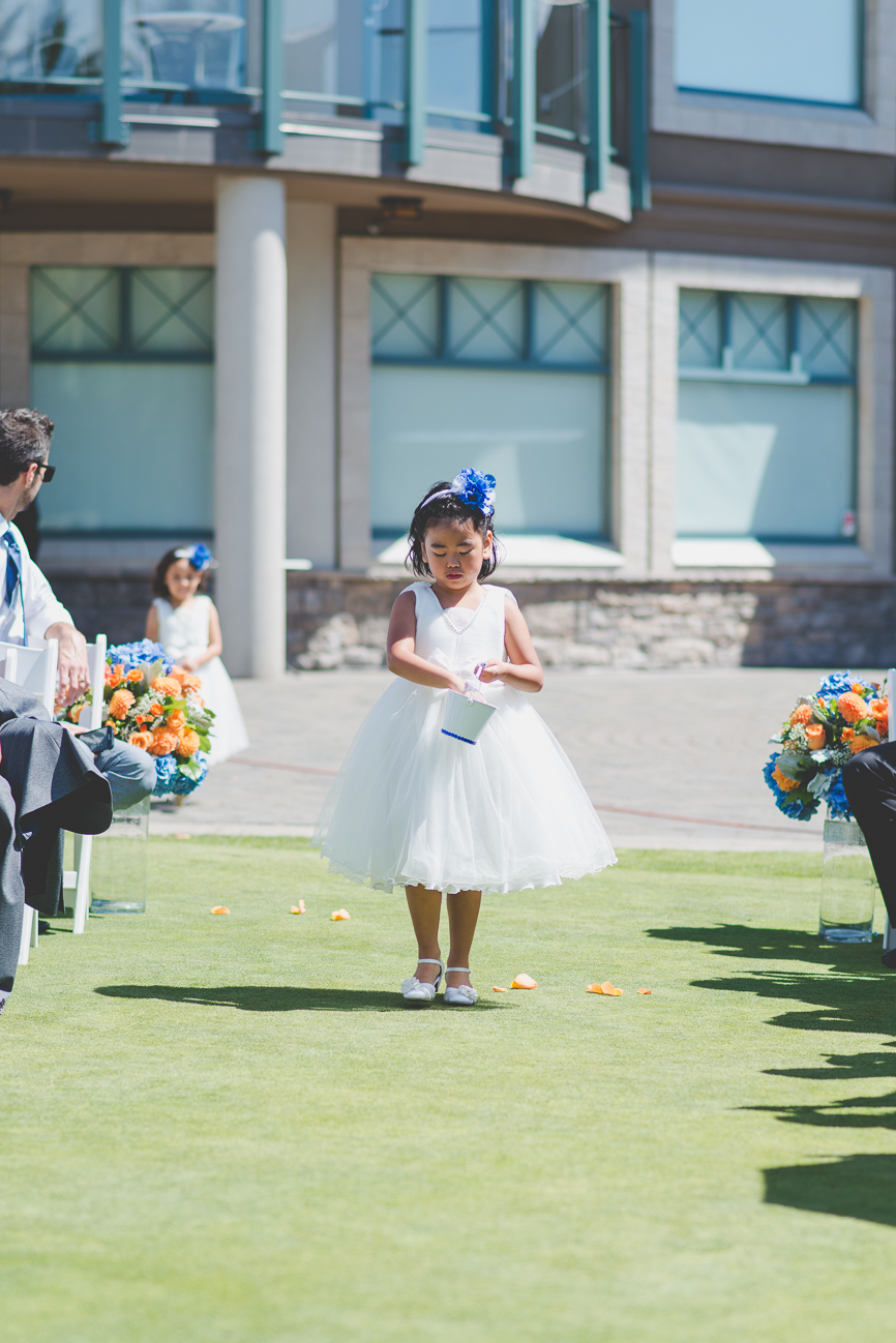 flower girl walking down the aisle at golf course wedding ceremony