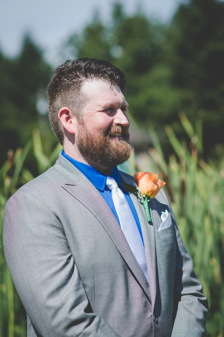 groom in grey suit with cobalt blue shirt, white tie and white pocket square seeing bride for the first time