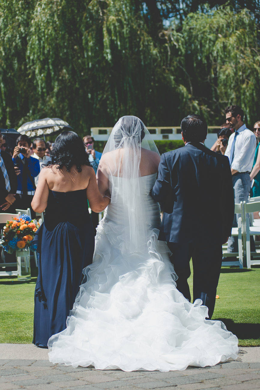 bride in ruffled wedding dress walking down the aisle with both parents