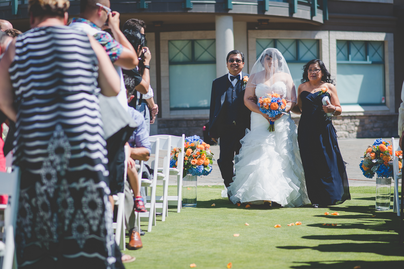 bride in sweetheart neckline ruffled wedding dress, hair flower, and veil crying walking down the aisle