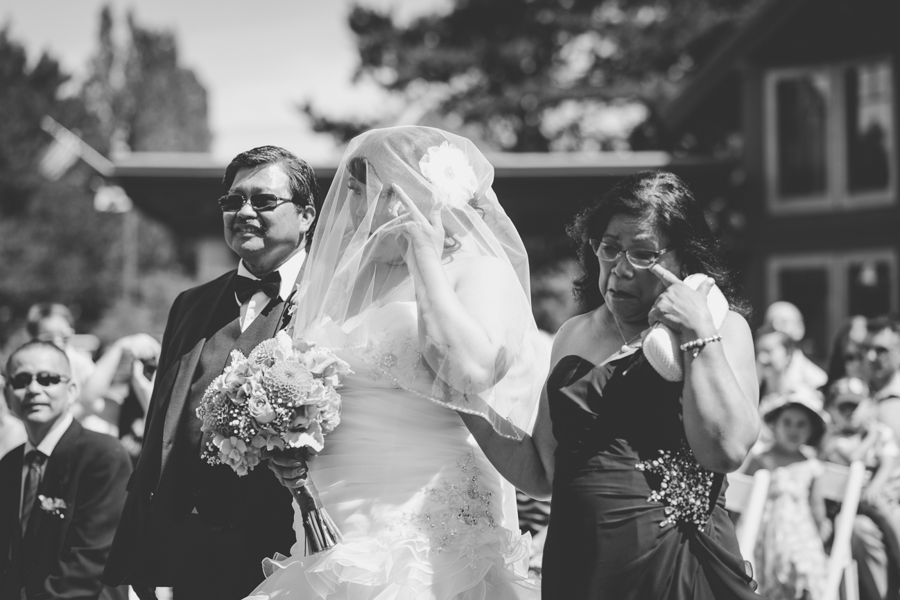 bride in sweetheart neckline ruffled wedding dress, hair flower, and veil crying with mother of the bride while walking down the aisle