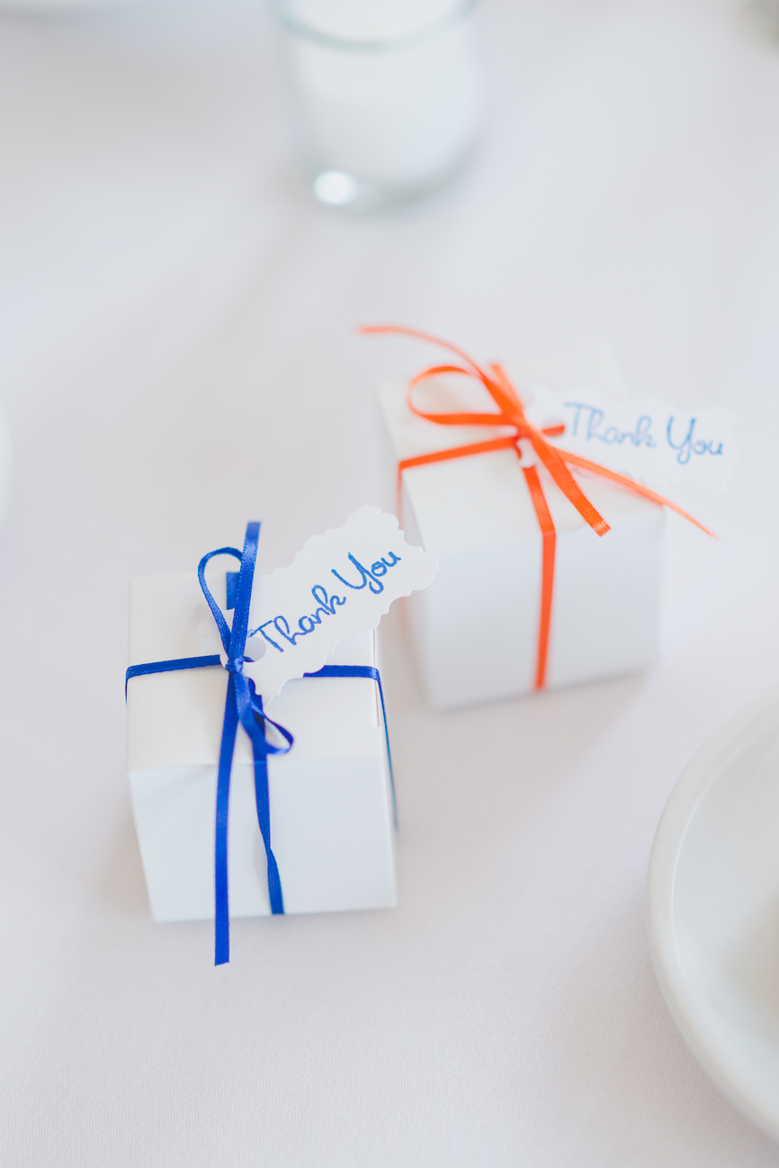 white wedding favour boxes with thank you tags and blue and orange ribbon