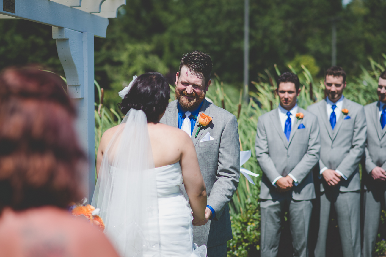 groom in grey suit with cobalt blue shirt, white tie and white pocket square, and orange rose boutonniere laughing during wedding ceremony