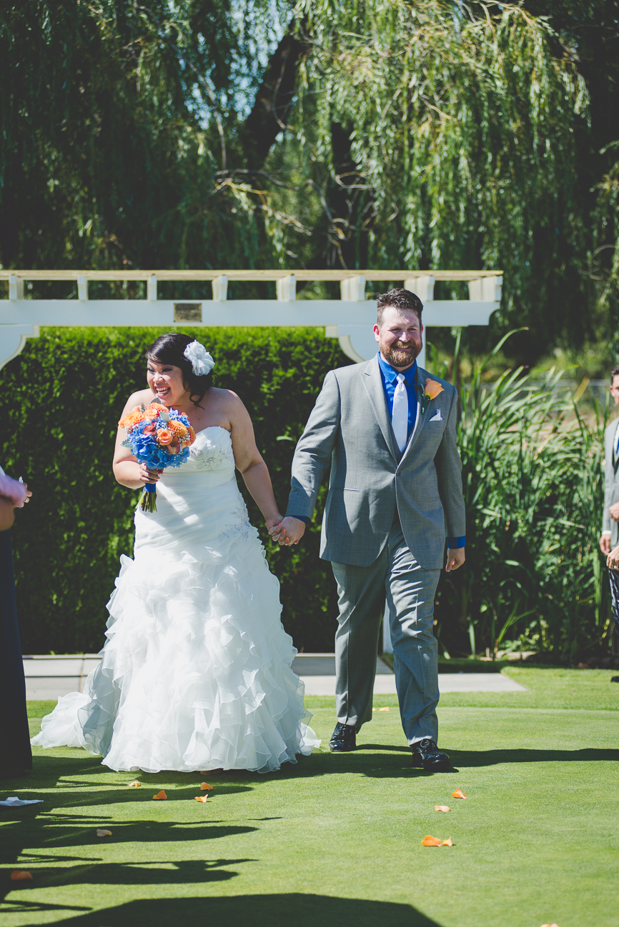 groom in grey suit with cobalt blue shirt, white tie, and orange rose boutonniere and bride in sweetheart neckline ruffled wedding dress and hair flower announced husband and wife