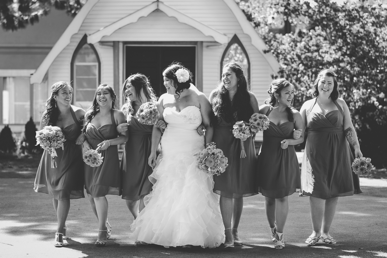 bride in sweetheart neckline wedding dress, hair flower, and orange and blue rose and dahlia bouquet walking and laughing with bridesmaids in cobalt blue halter cocktail bridesmaid dresses