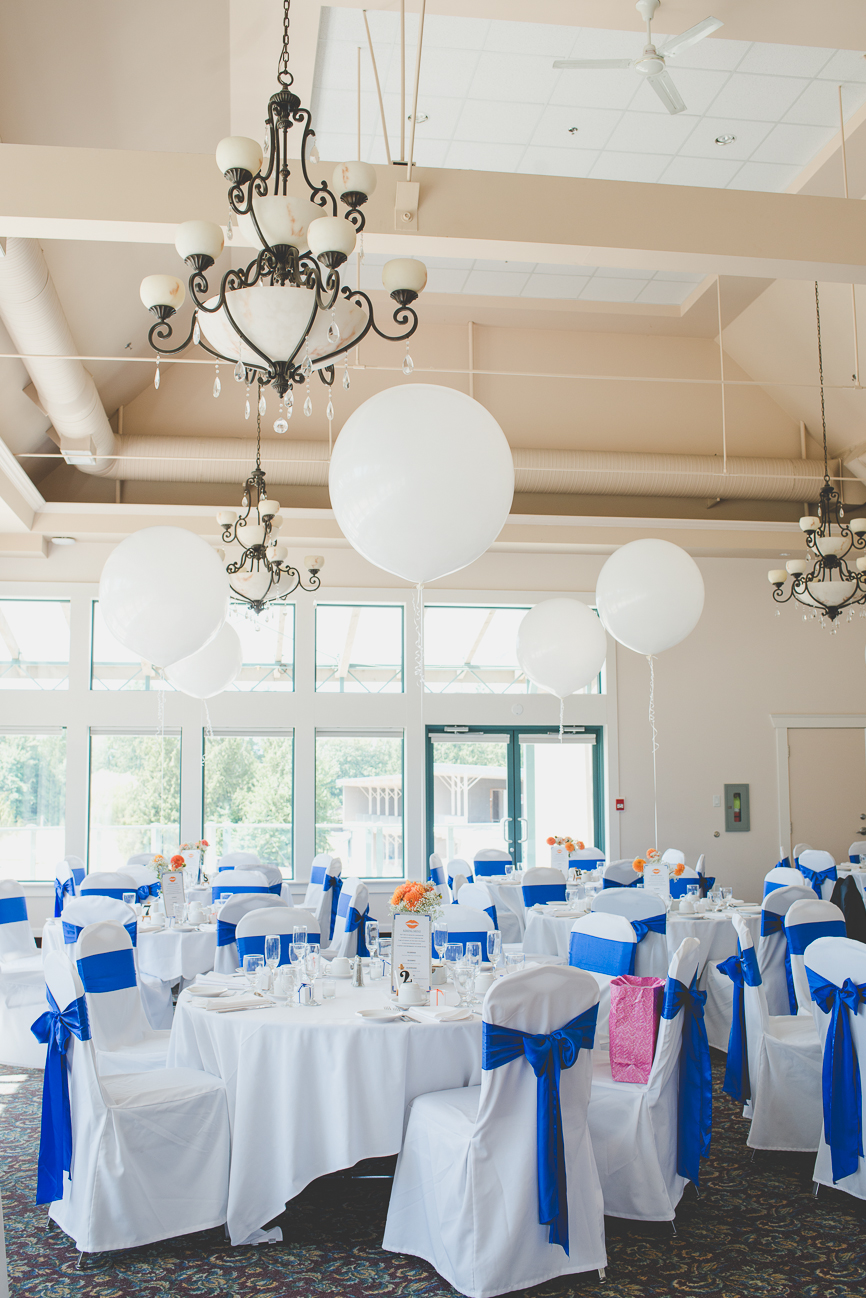 white chair covers with cobalt blue sashes with orange dahlia centerpieces with giant white balloons at wedding reception