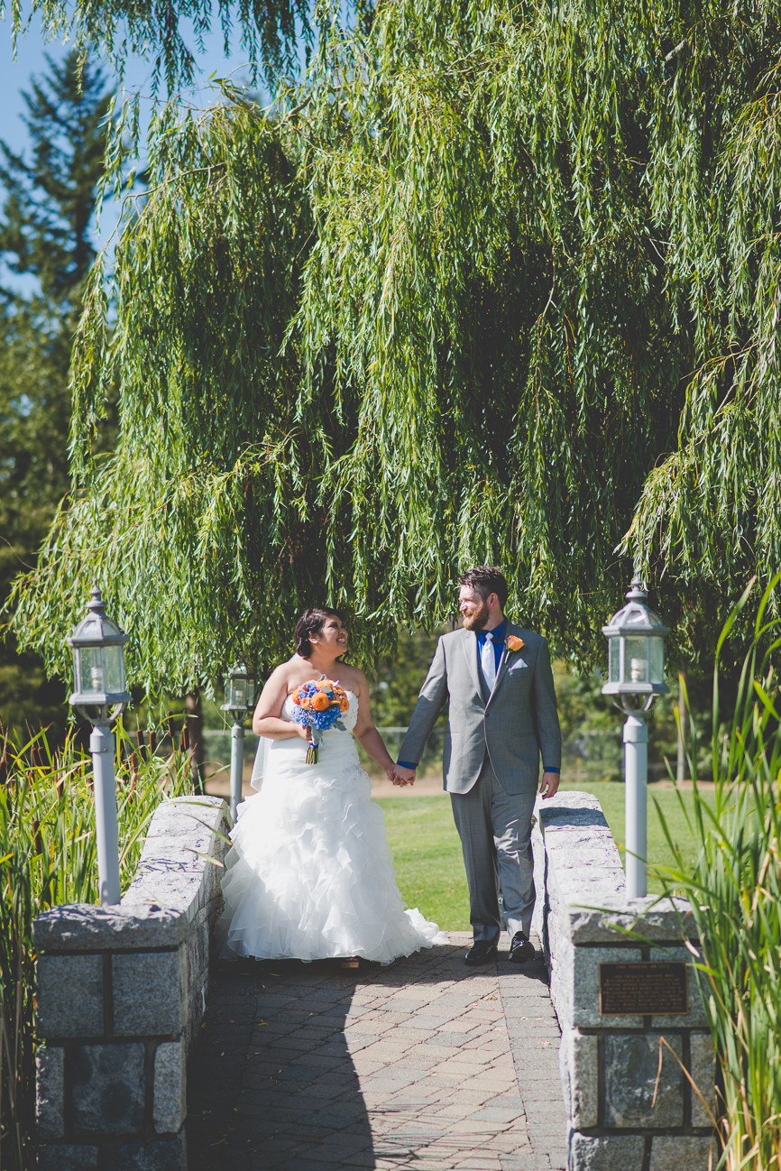 groom in grey suit with cobalt blue shirt, white tie, and orange rose boutonniere and bride in sweetheart neckline wedding dress, hair flower, and orange and blue rose and dahlia bouquet on stone bridge at golf course