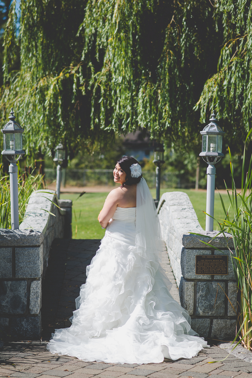 bride in sweetheart neckline wedding dress, hair flower, and orange and blue rose and dahlia bouquet on stone bridge at golf course