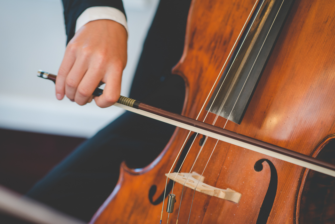 cellist playing cello during cocktail hour at wedding reception