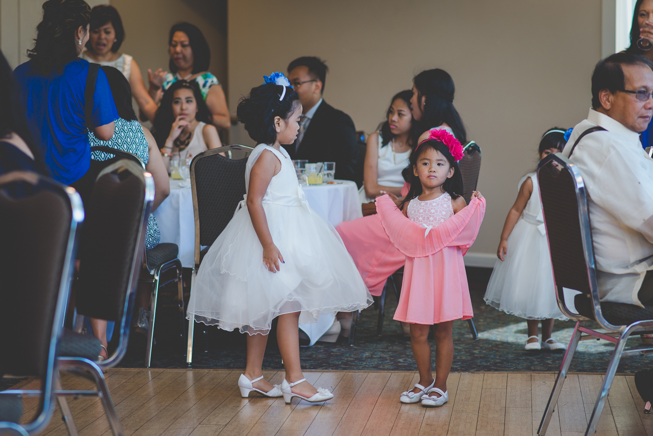flower girl and child guest wearing flower headbands lifting up dresses during cocktail hour at wedding reception