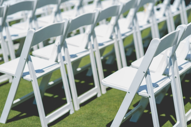 white wooden chairs at golf course wedding ceremony