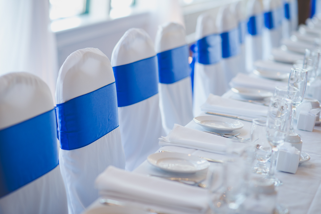 chairs in white chair covers and cobalt blue sashes at wedding reception