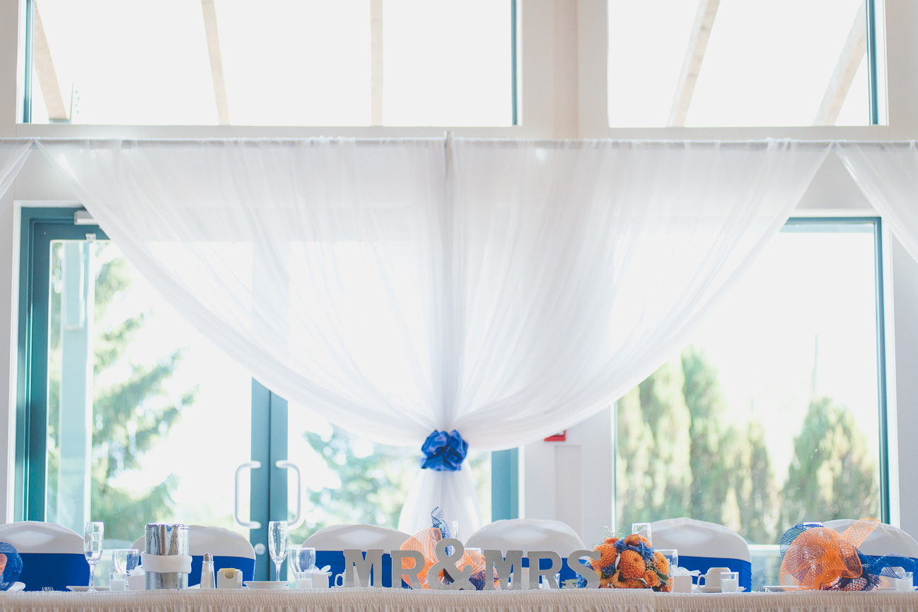 head table with wooden Mr & Mrs sign with translucent white curtains and cobalt blue chair sashes
