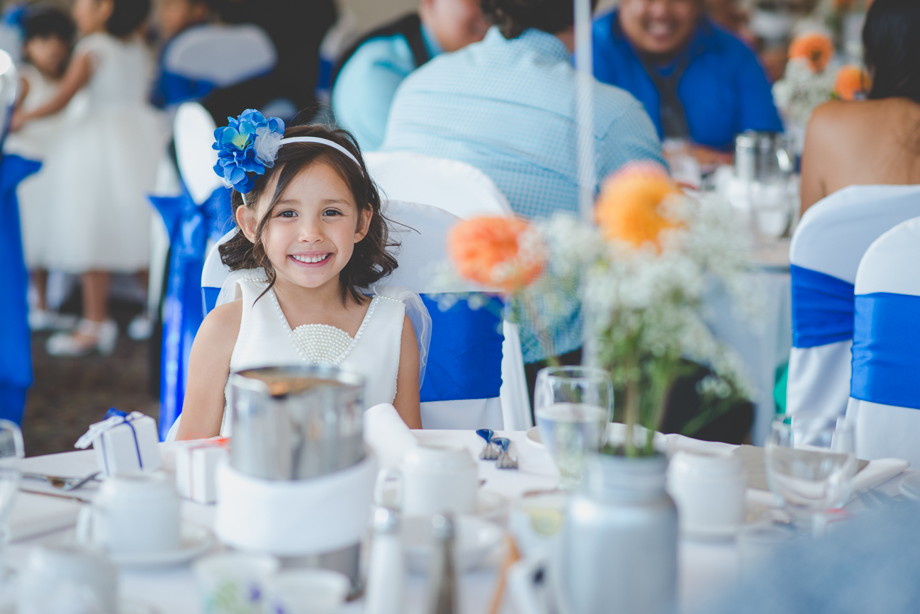 flower girl wearing headband with blue flower sitting on chair with white chair cover and cobalt blue sash at wedding reception