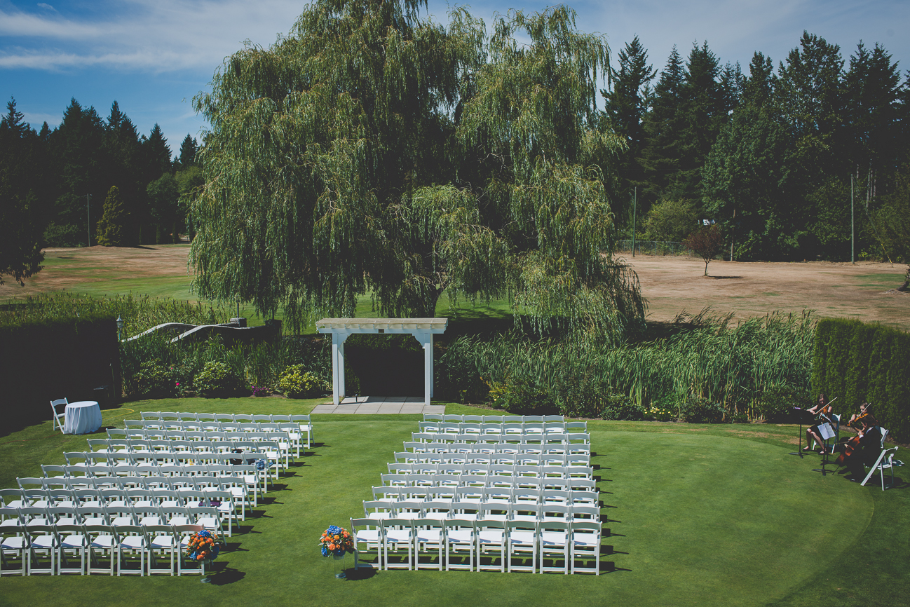 white wooden chairs and white archway under willow tree at golf course wedding ceremony
