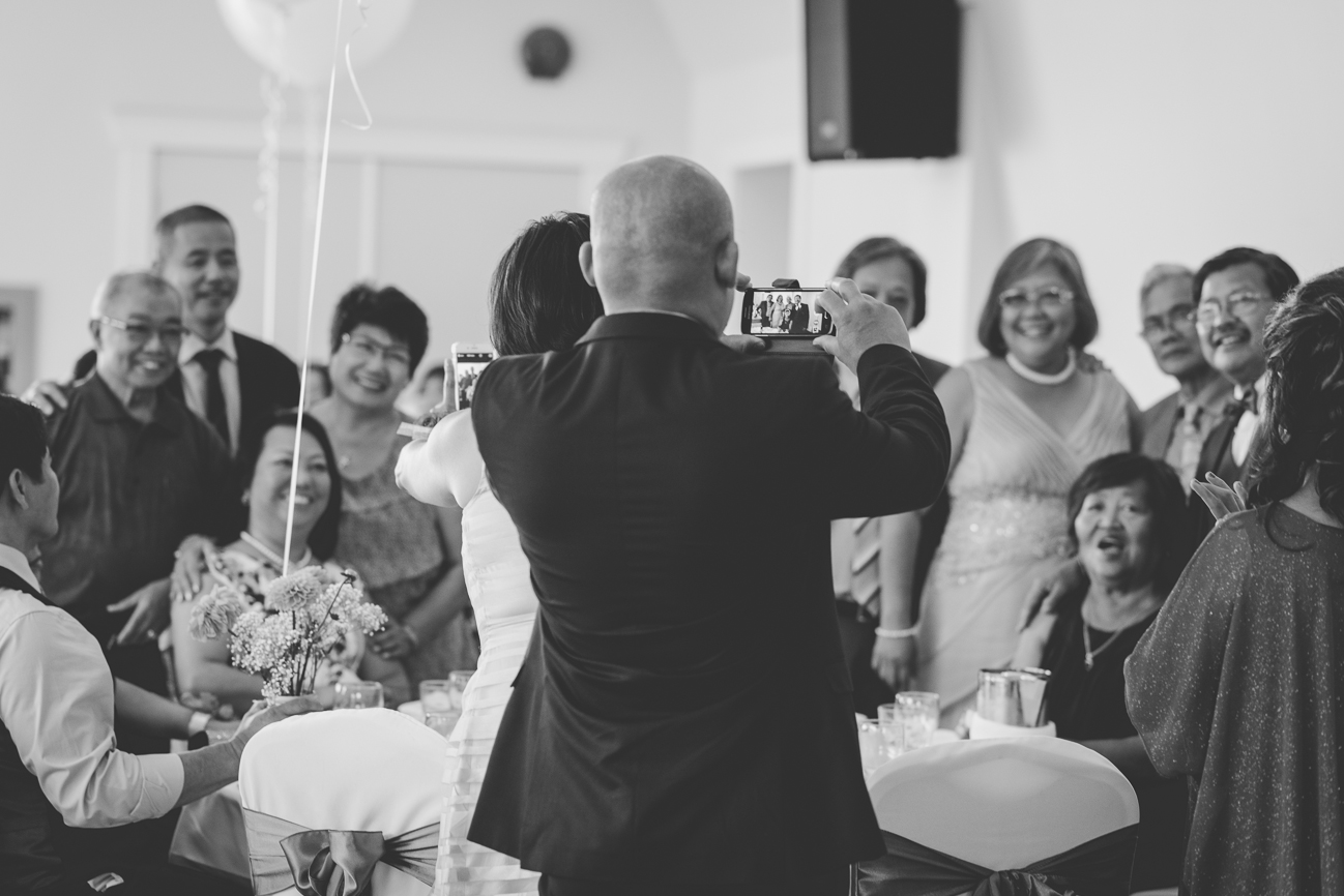 guests taking group photos at wedding reception