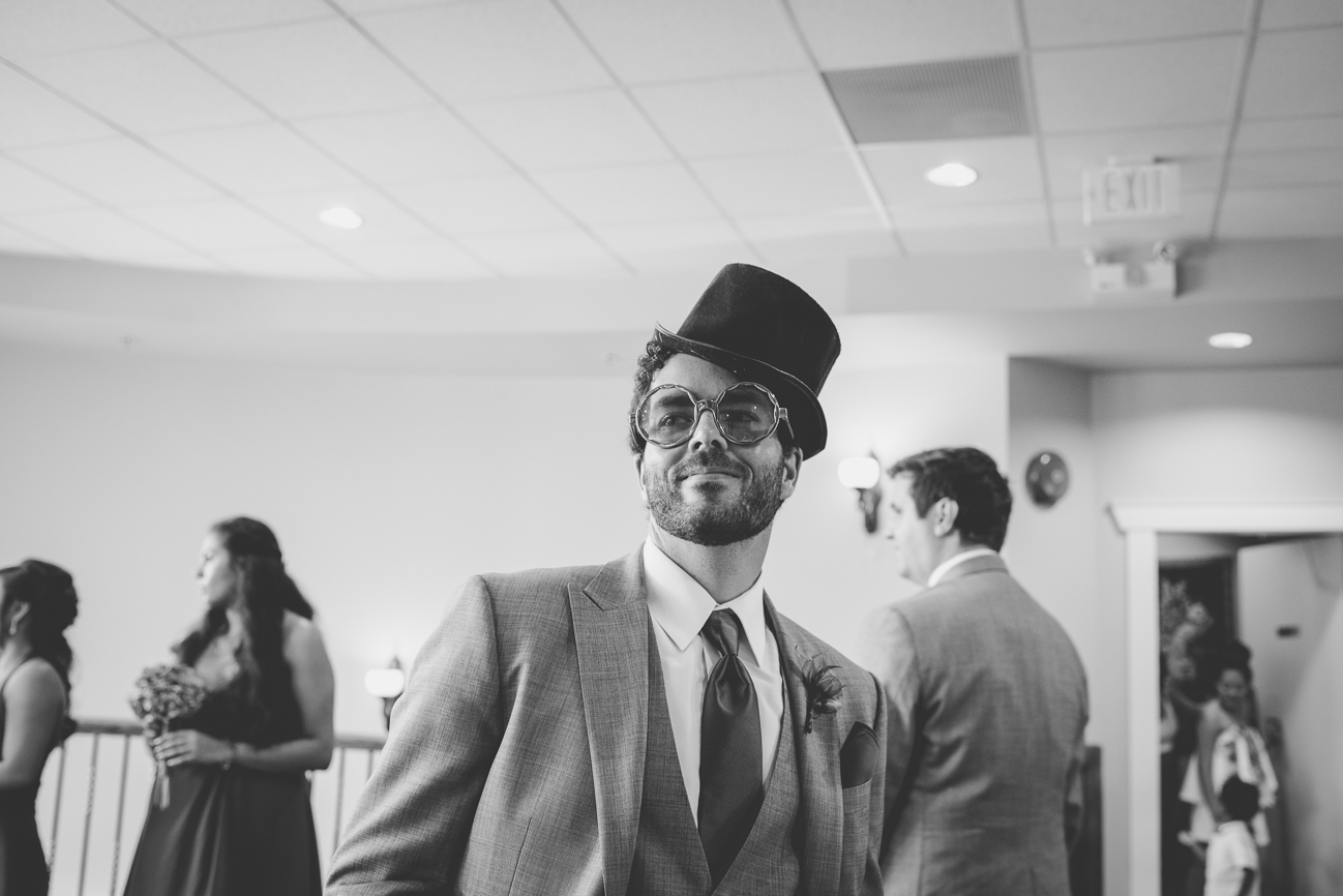 groomsman wearing top hat and big sunglasses from photo booth during cocktail hour at wedding reception