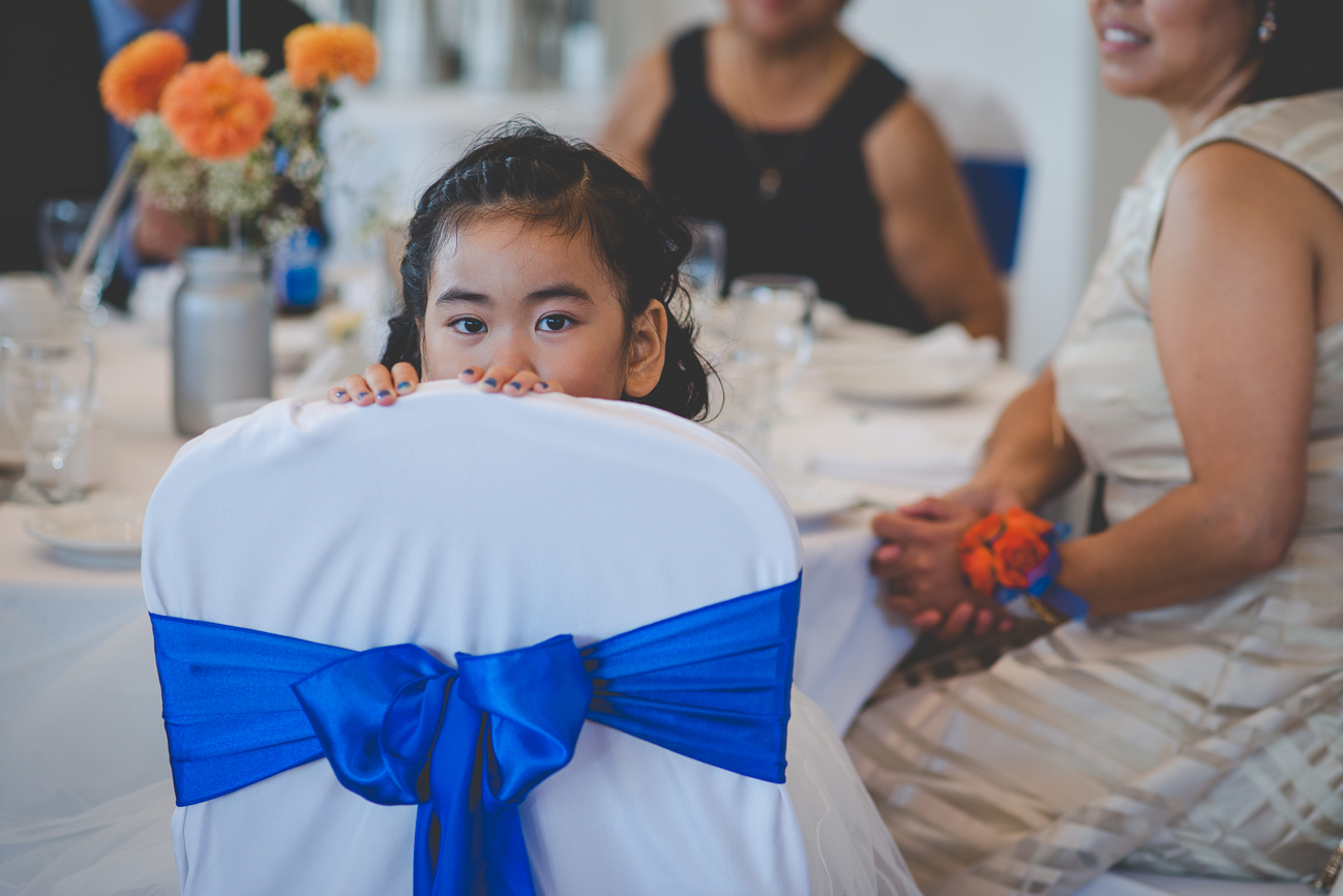 flower girl wearing blue nail polish peeking over chair with white chair cover and cobalt blue sash at wedding reception