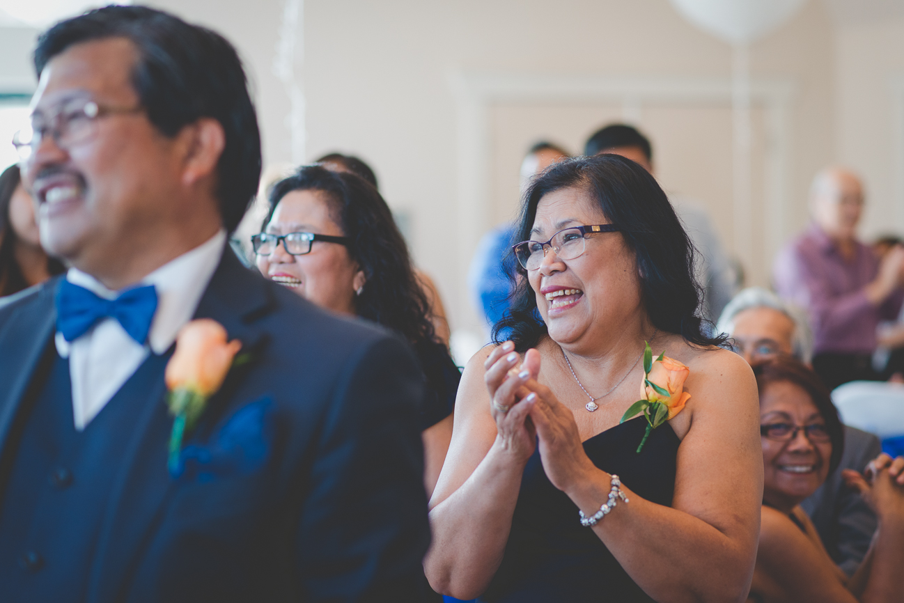 mother of the bride wearing orange rose corsage clapping during grand entrance at wedding reception