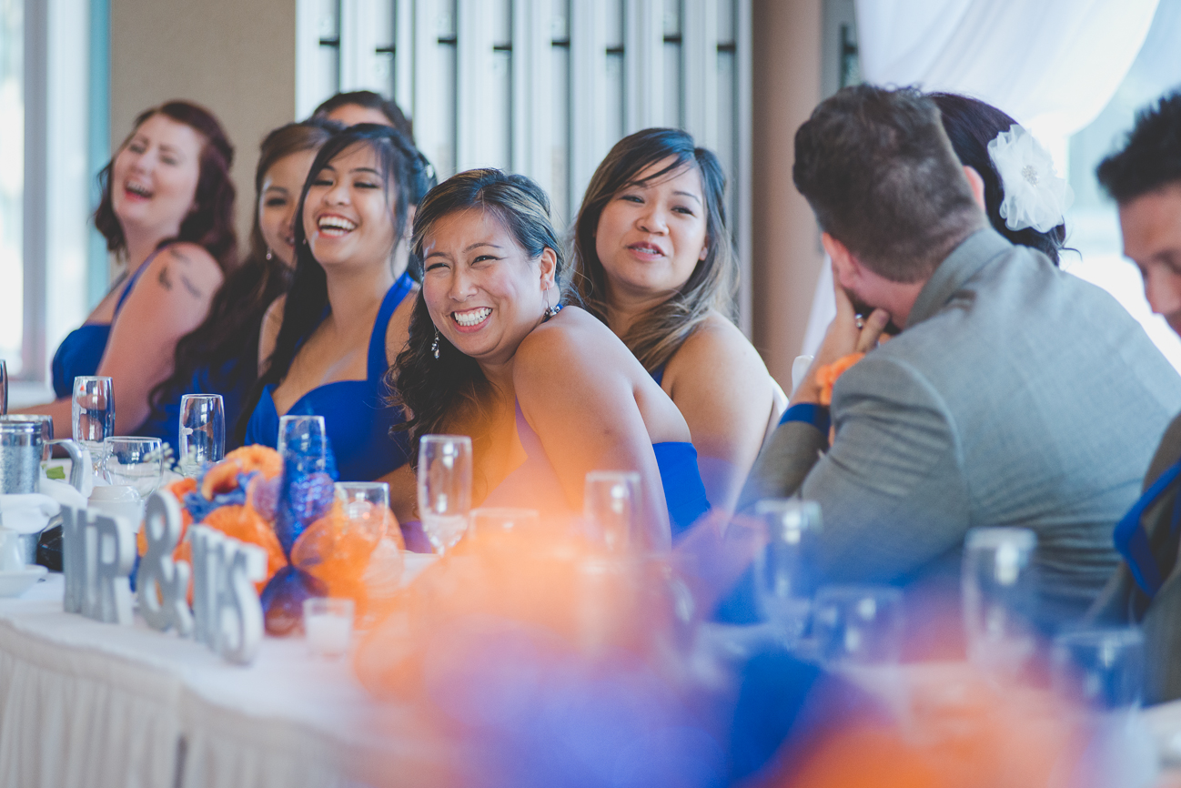 bridesmaids in halter cocktail blue bridesmaids dresses laughing at head table during wedding reception