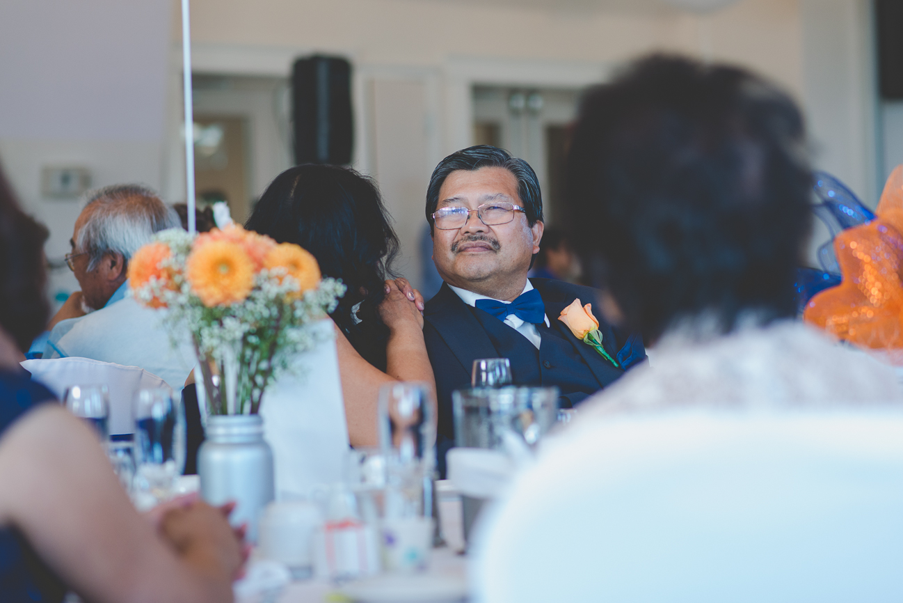father of the bride in blue bow tie and orange rose boutonniere and mother of the bride at wedding reception